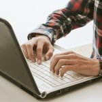 Male in plaid shirt typing on laptop