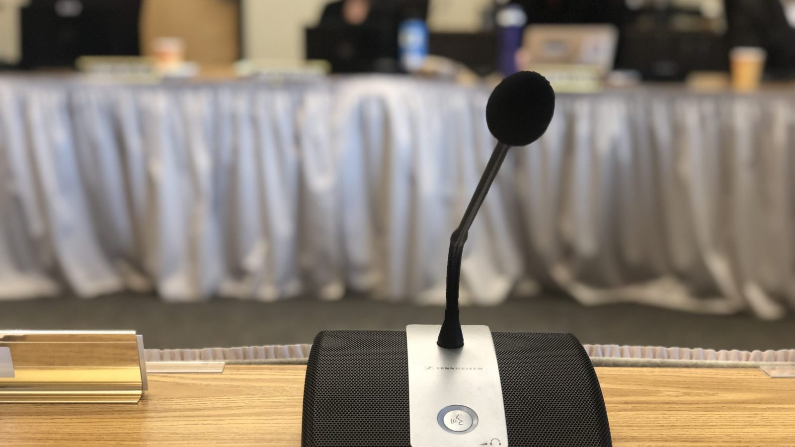 microphone on a table, people sitting in background