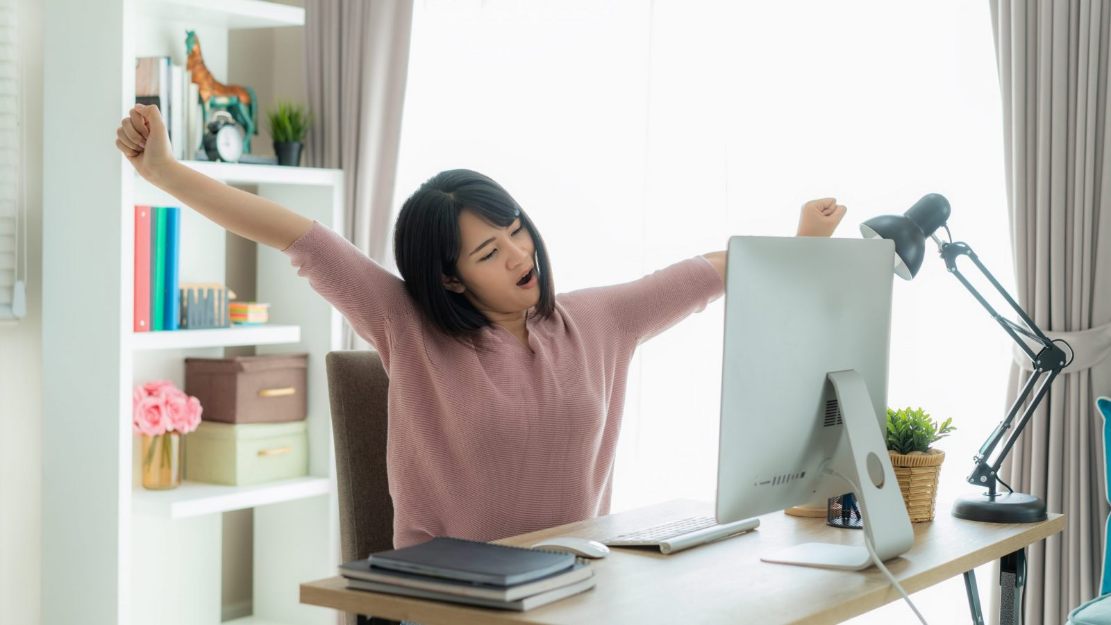 Woman stretching at computer