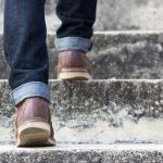 person wearing jeans, walking up stairs