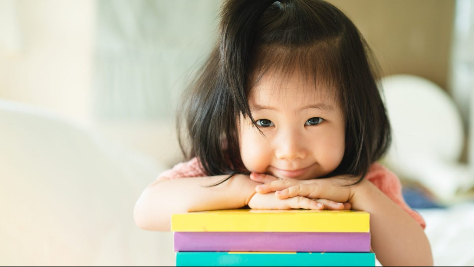 Toddler girl leaning on a stack of books.