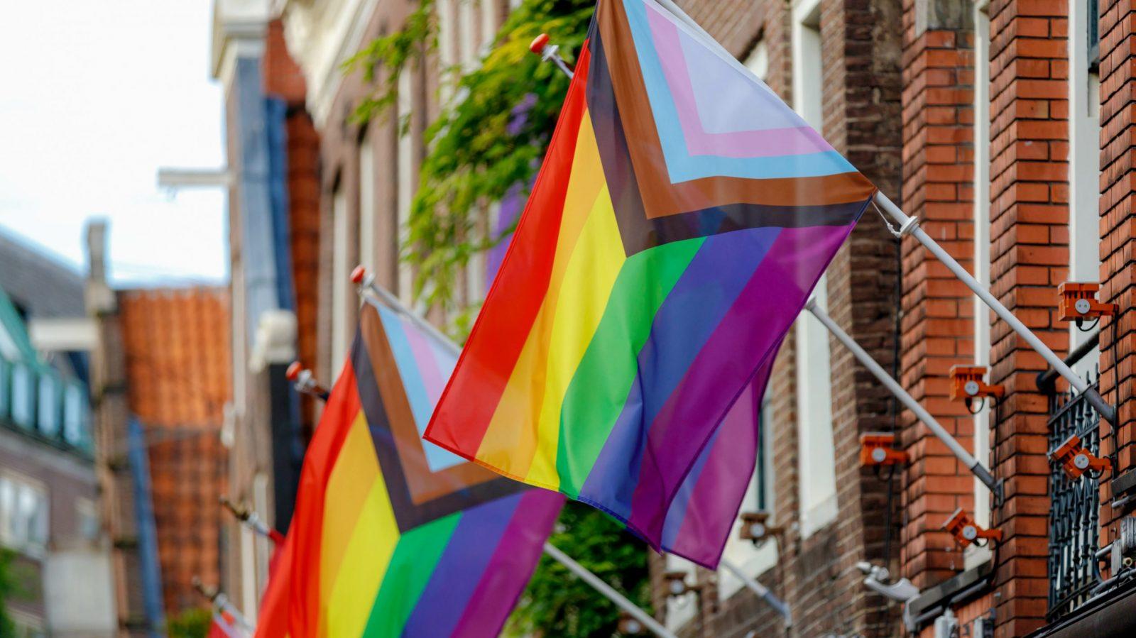 Progress pride flag on city street